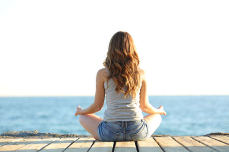 Photo pour Back view portrait of a teenage girl practicing yoga exercises on the beach - image libre de droit
