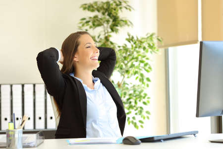 Photo pour Satisfied office worker enjoying at workplace looking away through a window - image libre de droit