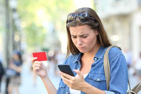 Foto de Worried girl having problem paying online with credit card and smart phone in the street - Imagen libre de derechos