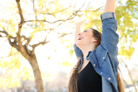 Photo pour Excited woman raising arms celebrating success in a park with trees in the background - image libre de droit
