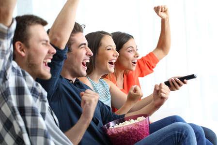 Foto de Four excited friends watching tv celebrating success sitting on a coucn at home - Imagen libre de derechos