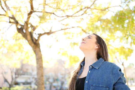 Photo pour Relaxed woman is breathing deep fresh air in a park with trees in the background - image libre de droit
