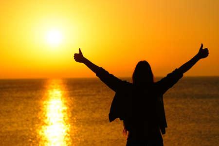 Foto de Back view portrait of a happy woman silhouette gesturing thumbs up outstrestching arms celebrating success at sunrise - Imagen libre de derechos
