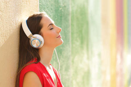Photo pour Side view portrait of a relaxed woman listening to the music in a colorful street - image libre de droit