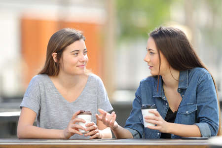 Photo pour Two casual friends talking in a park drinking coffee - image libre de droit
