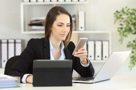 Photo for Busy businesswoman using multiple devices a phone laptop and tablet at office - Royalty Free Image