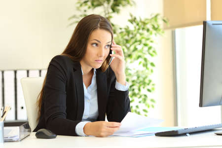 Photo for Confused businesswoman talking on phone watching computer content trying to understand at office - Royalty Free Image