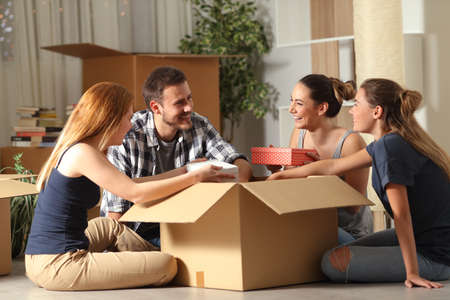 Photo for Happy roommates unboxing belongings moving home sitting on the floor in the night - Royalty Free Image