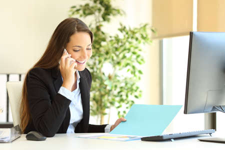 Photo pour Happy office worker checking document talking on phone at workplace - image libre de droit