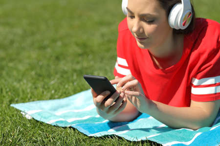 Photo pour Serious girl in red listens to music browsing smart phone content on the grass - image libre de droit