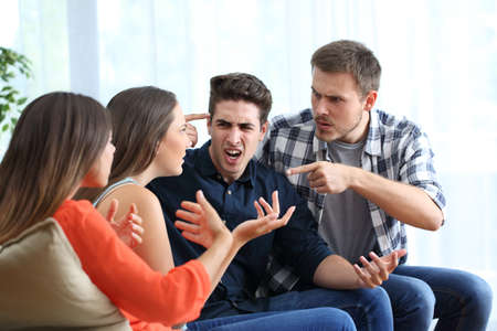 Photo pour Four angry friends arguing accusing each others at home - image libre de droit