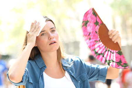 Photo for Sad woman fanning and sweating suffering a heat stroke on summer in the street - Royalty Free Image