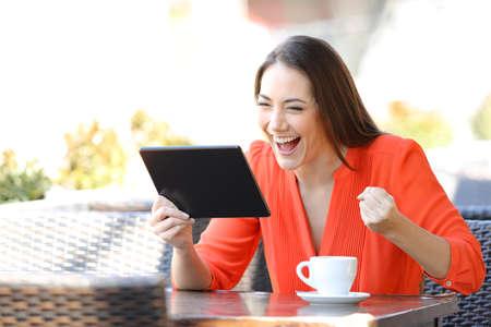 Foto de Excited woman finding online offers on tablet sitting in a coffee shop terrace - Imagen libre de derechos