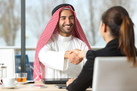 Photo for Front view of an arab businessman and marketer handshaking in a coffee shop or hotel bar - Royalty Free Image