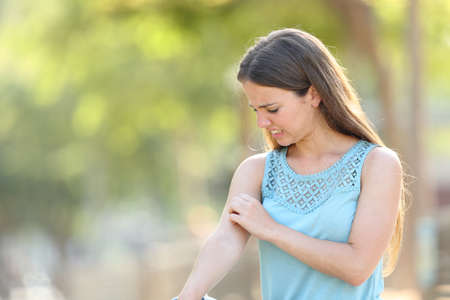Photo pour Woman scratching arm because it stings in a park with a green background - image libre de droit