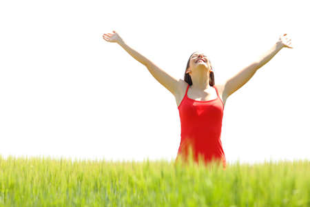 Photo pour Front view portrait of a happy woman celebrating success raising arms in a field with a white isolated background above - image libre de droit