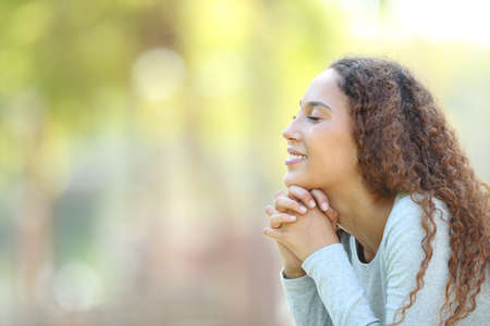 Photo pour Side view portrait of a happy mixed race woman meditating and breathing fresh air outdoors in a park - image libre de droit