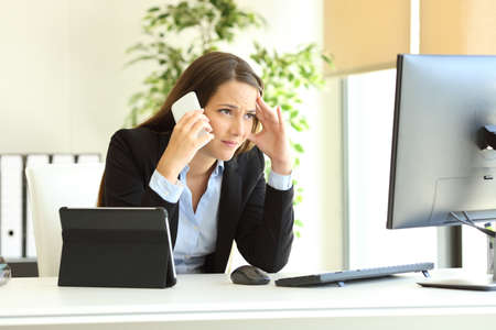 Photo for Worried office worker using multiple devices calling on phone at workplece - Royalty Free Image