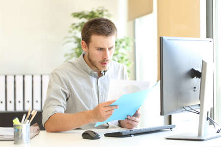 Photo for Shocked businessman checking documents with bad news at office - Royalty Free Image