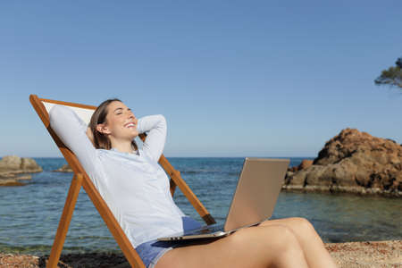 Photo for Happy entrepreneur sitting on a deck chair with a laptop relaxing on the beach - Royalty Free Image