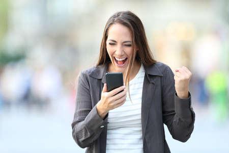 Foto de Front view portrait of excited woman checking smart phone on line content in the street - Imagen libre de derechos
