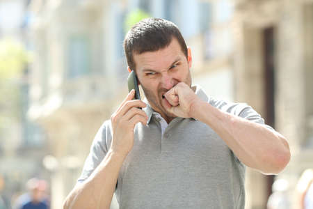 Photo for Angry man talking on mobile phone having problems standing in the street - Royalty Free Image