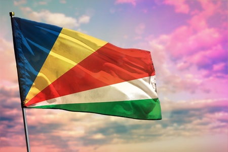 Photo for Fluttering Seychelles flag on colorful cloudy sky background. Seychelles prospering concept. - Royalty Free Image
