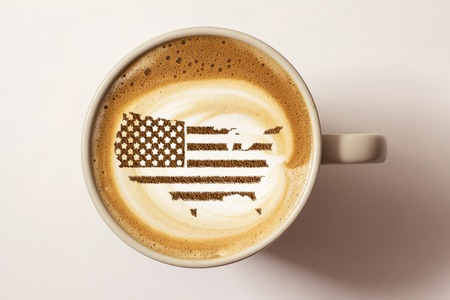 Foto de Flag of the United States of America in the form of territorial borders on a cappuccino coffee cup close-up - Imagen libre de derechos