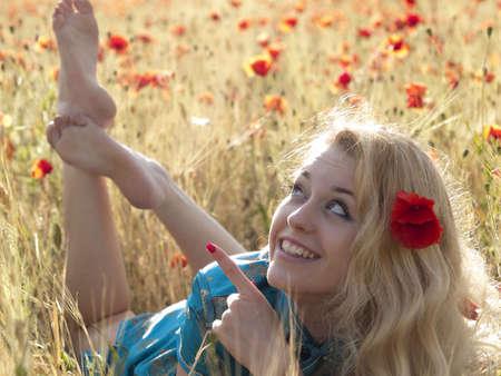 Beautiful Barefoot blonde lady laying in poppy field