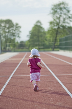 Photo for little girl runs across the track - Royalty Free Image