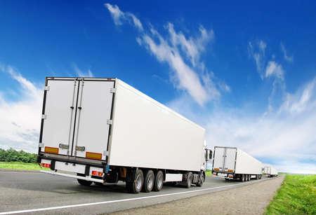 caravan of white trucks on country highway under blue sky