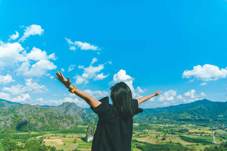 Foto de Woman rise hands up to sky freedom concept with blue sky and summer field background. - Imagen libre de derechos