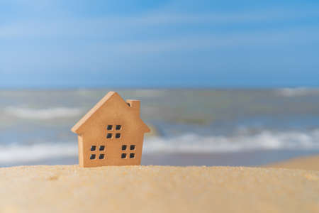 Foto de Closed up tiny home models on sand with sunlight and beach background. - Imagen libre de derechos