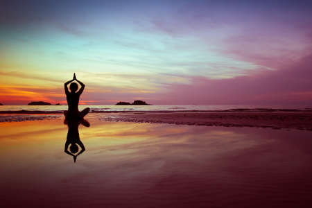 Foto de woman practices yoga on the beach at sunset - Imagen libre de derechos