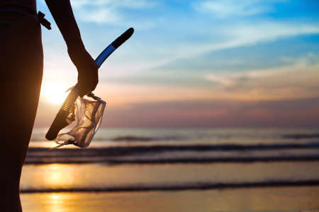 Foto de diving, silhouette of hand with equipment for snorkeling, on the beach - Imagen libre de derechos