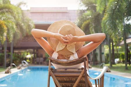 Photo pour woman in hat taking sunbath near swimming pool - image libre de droit
