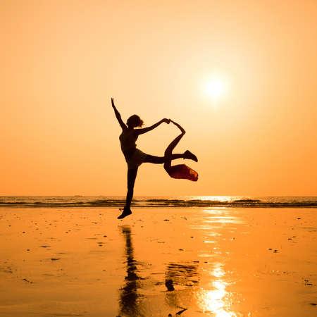 Photo pour silhouette of dancing woman on the beach - image libre de droit