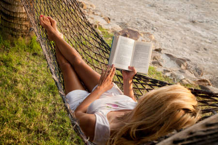 Foto de Woman lying in a hammock on the beach and enjoying a book reading - Imagen libre de derechos