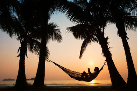 Photo for silhouette of woman relaxing in hammock with the book - Royalty Free Image