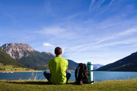 Foto de hiking in mountains, young traveller meditate near the lake,  contemplation - Imagen libre de derechos