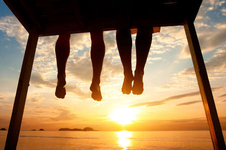 Photo pour silhouette of feet of couple sitting on the pier at sunset beach, low angle view - image libre de droit