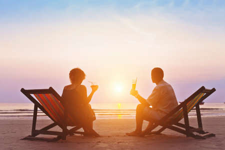 Foto de family enjoying romantic sunset on the beach - Imagen libre de derechos