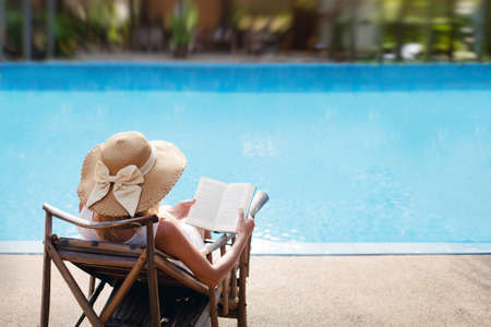 Photo for woman reading and relaxing near luxury swimming pool - Royalty Free Image