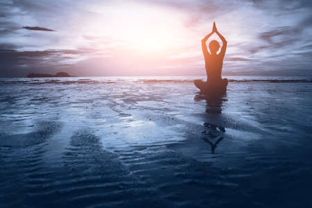 Foto de well being concept, beautiful sunset on the beach, woman practicing yoga - Imagen libre de derechos