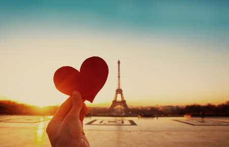 Foto de beautiful vintage card from Paris, Eiffel tower and hand with paper heart at sunrise - Imagen libre de derechos