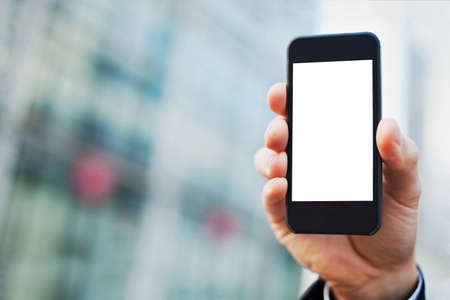 Foto de hand of business man with smartphone on office buildings background - Imagen libre de derechos
