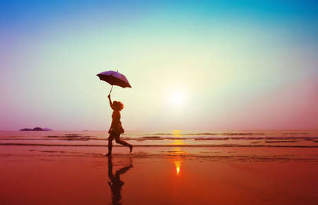 Photo pour happy woman jumping with umbrella on the beach - image libre de droit