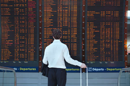 Photo for passenger looking at timetable board at the airport - Royalty Free Image