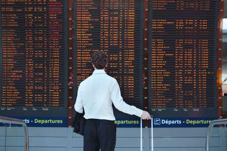 Photo pour passenger looking at timetable board at the airport - image libre de droit