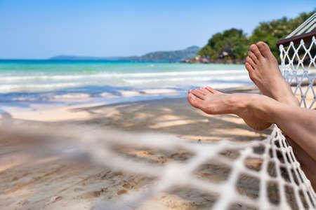Photo pour woman feet in hammock on the beach - image libre de droit